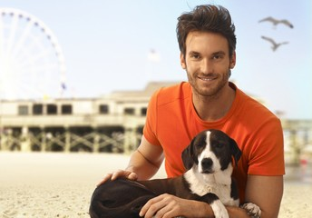 Happy handsome man with dog at seascape beach