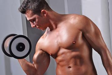 Hombre fuerte entrenando brazo con pesas en gimnasio.