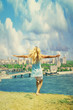 girl standing arms outstretched on the river bank