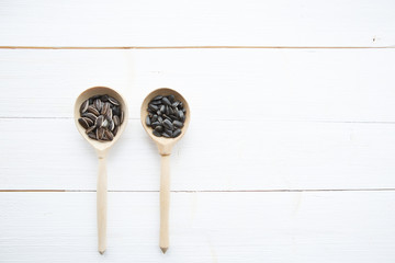 Sunflowers seeds in spoon on white wooden table