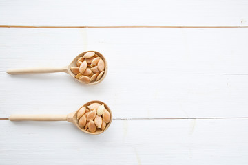 Pumpkin seeds in spoon on white wooden table