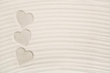 Drei Herzen im Sand als Hintergrund