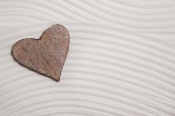 Ein Holz Herz im Sand als Hintergrund für eine Grußkarte
