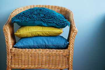 Blue and yellow cushions lie on a straw chair