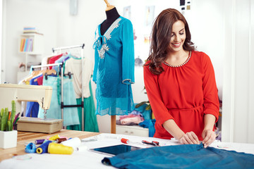 Young female designer measuring textile material