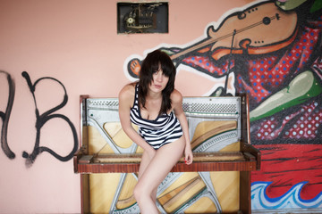 brunette in striped top near the broken piano in an abandoned ro