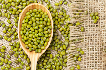 Heap of organic raw green mung bean lentils in wooden spoon