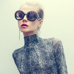 Woman in fashionable sunglasses. Animal print trend