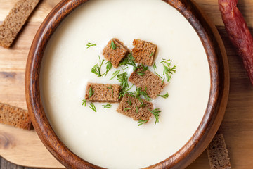 White cream soup with dill croutons and sausage in wooden bowl