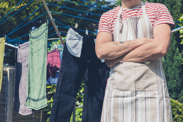 Young man by clothes line in garden