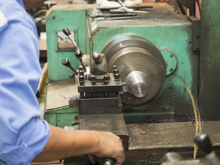 operator turning mold parts by manual lathe