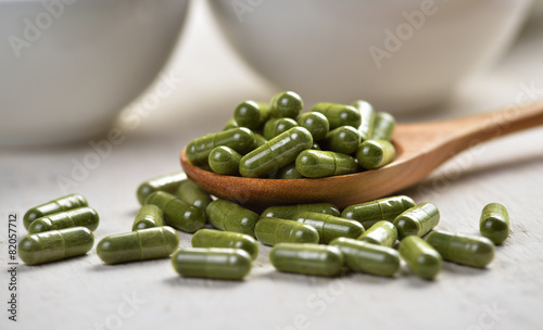Moringa capsule pills in the woodspoon - 82057712