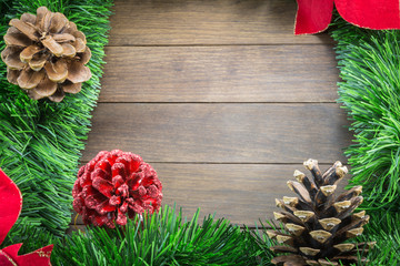 christmas decoration with pine cones and poinsettia on wooden ba