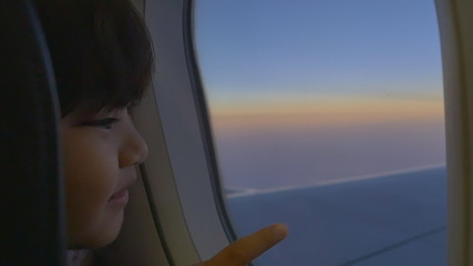 Happy little Asian girl looking outside the window of airplane