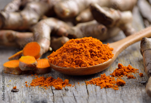 pile of fresh turmeric roots on wooden table - 82058970