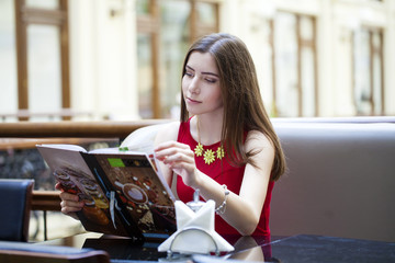 Beautiful girl sitting in a cafe and considers the menu