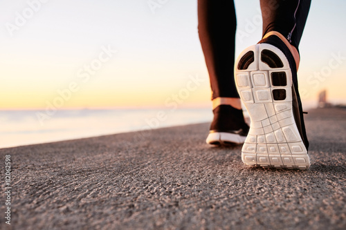 canvas print picture Runner man feet running on road closeup on shoe.