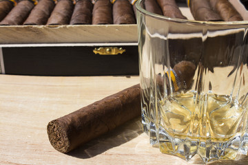half-empty glass of brandy and cigars