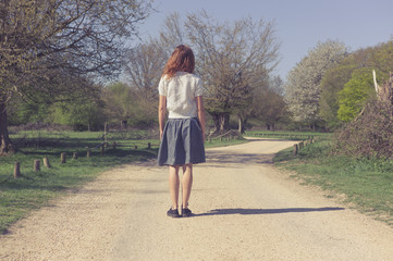 Woman standing on dirt road in forest