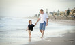 young happy father holding hand of little son walking on beach