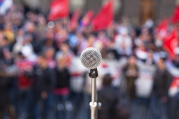 Microphone in focus against unrecognizable crowd of people