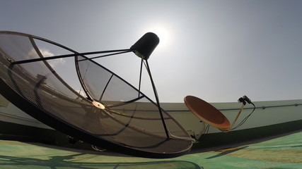 Satellite dish with sun sky - Panning video