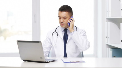 happy doctor with laptop calling on smartphone