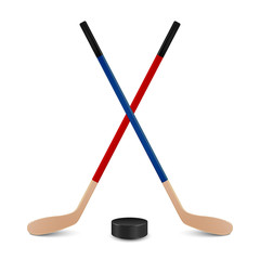 Two crossed hockey sticks and puck.