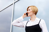 Blonde businesswoman calling by smartphone