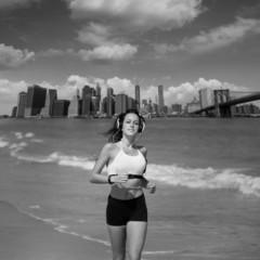 Brunette girl running in New York Brooklyn bridge