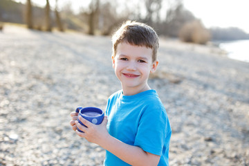 Little boy holding clean water in dotted mug