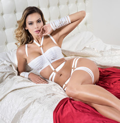 Bride on the bed in white erotic lingerie