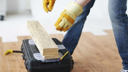 close up of man hammering nail to wooden board