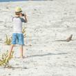Little boy photographing iguana