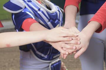 A baseball team puting hand together