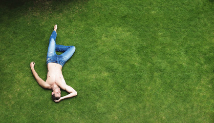 Relaxing man lying on the green grass in the meadow