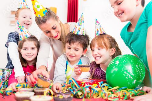 Kind erhält Geschenk zum Kindergeburtstag - 82076918