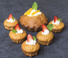 Carrot cupcakes with strawberries and mint on a blue background