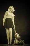 childlike woman with dog toy on black poster