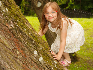Little girl playing in park climbing to e tree.