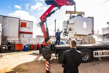 Crane truck lifting heavy CNC machine with hydraulic arm