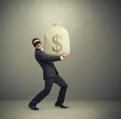 man holding big bag with money