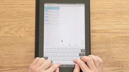 Female hands typing message on tablet computer
