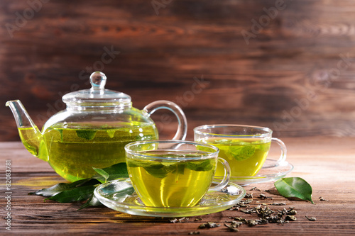 Fototapeta Cups of green tea on table on wooden background