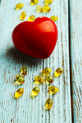 Red heart and cod liver oil on blue wooden background