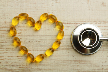 Heart of cod liver oil and stethoscope, on wooden background