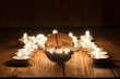 Glass transparent ball and burning candles on old wooden