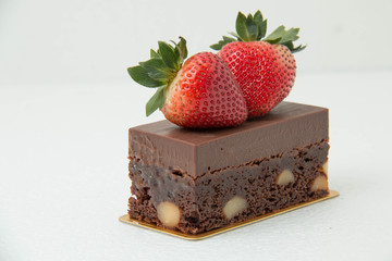 A Brownie desert with strawberries on top.