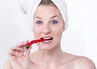 Junge Frau mit einer Chilischote im Mund