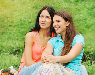 two happy smiling women friends on picnic at the park
